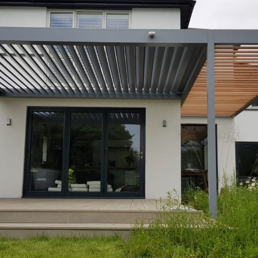 grey aluminium louvre roof and wood effect patio louvre roof combined for a unique outdoor garden roof solution