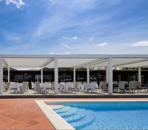 hotel pool wit poolside dining areas covered by Louvre roofs in a modular configurations