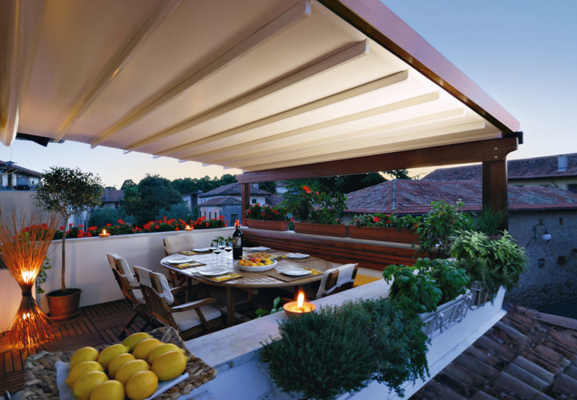 cozy alfresco dining area on a rasidential blacony with a retractable awning roof for shade and water protection